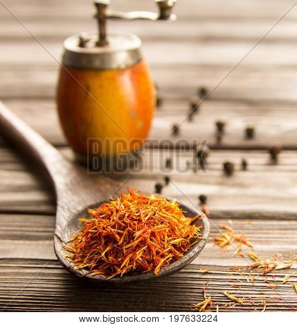 Spice saffron in a wooden spoon on a wooden backgroundbehind vintage handmill and spice pepper. Close-up.
