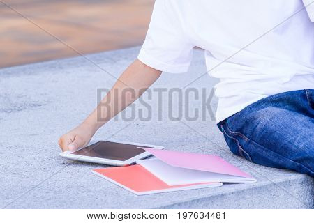 Kid's hand digital tablet computer and books. Boy sitting and leaning on closed books