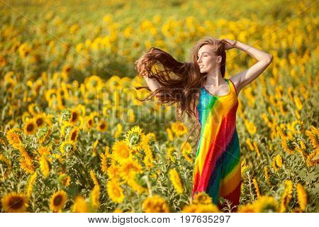 Woman's hair is fluttering in the wind she is standing in the field of sunflowers.