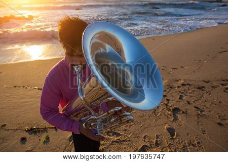 Musician playing the Tuba on the sea coast during an amazing sunset.