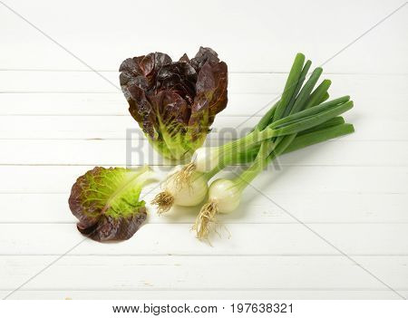 bunch of spring onions and head of fresh lettuce on white wooden background