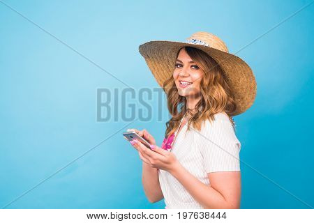 Technology, people and modern devices concept - Smiling Woman writing in phone, texting message on blue background with copy space