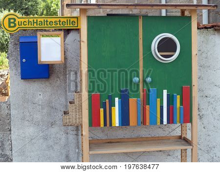 A small outdoor colorful book case and sign with german text for book stop