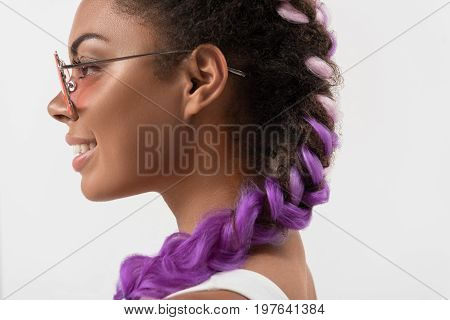 Modern look. Close up profile of cheerful african girl in sunglasses is demonstrating her purple synthetic braids using kanekalon hair. Isolated background