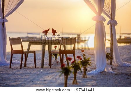 Romantic dinner setting on the tropical beach at sunset