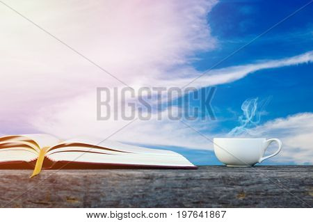 Book and coffee cup on wooden table textured with cloud sky background.Education concept.