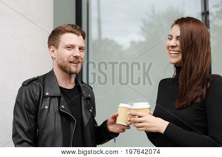 Picture of two best friends relaxing outdoors on sunny day drinking takeaway coffee having fun laughing at each other's jokes. Bearded hipster treating charming brunette girl to good coffee