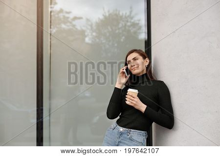 Beautiful student girl in black turtleneck and blue jeans leaning on conceret wall talking on smart phone and holding takeaway coffee in papercup listening to her interlocutor with interest smiling