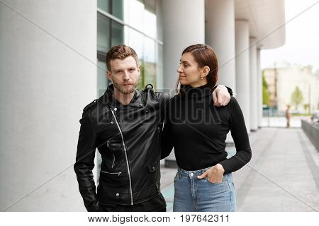 Beautiful young couple in love dating walking on city streets. Pretty girl having walk in urban surroundings with her stylish bearded man hugging each other sharing sweet moments of being together