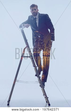 Achieving business success in city. Full length portrait of self-assured bearded man standing stern on the career ladder and looking at camera with confidence. Double exposure with manager and urban scene