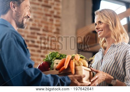 Convenient service. Inspired witty young lady receiving a box full of vegetables at home while courier brining it for her after she making an online order