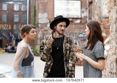 Candid shot of two beautiful stylish teenage girls having fight outdoors trying to win love of handsome hipster guy who is standing between them and saying to calm down. Love triangle concept