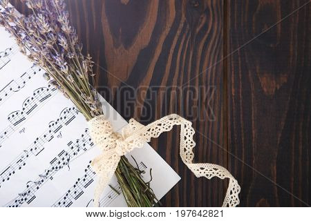 Lavender and paper music notes on old wooden background in vintage style top view.