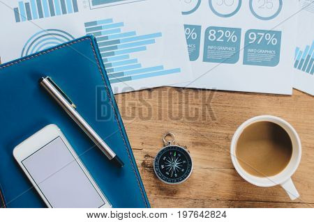 Table Top view of businessman  with compass, smart phone , pen ,notepad ,coffee cup and data report ,business and financial concept.