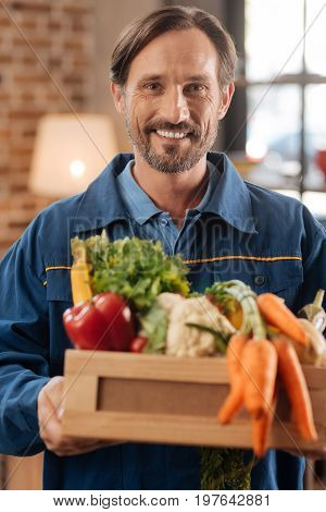 Driving all around the city. Sympathetic sincere nice man holding a box full of healthy vegetables while visiting clients home and delivering food