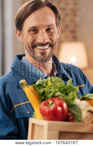 Keeping it healthy. Productive sincere excited guy providing delivery services while bringing people goods they purchasing from home