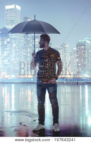 Thoughtful young man is holding umbrella under his head during rain in the city. He is standing near water with relaxation. Urban night nights on his body. Double exposure
