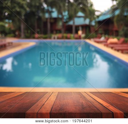 Empty brown wooden table surface and swimming pool blur background with bokeh image, for product display montage,can be used for montage or display your products.