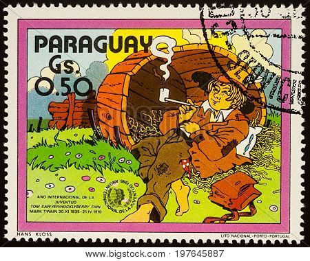 Moscow Russia - July 30 2017: A stamp printed in Paraguay shows Huckleberry Finn in the old barrel Adventures of Tom Sawyer by Mark Twain series