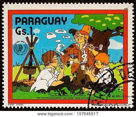 Moscow Russia - July 30 2017: A stamp printed in Paraguay shows Huckleberry Finn and Friends by Campsfire Adventures of Tom Sawyer by Mark Twain series