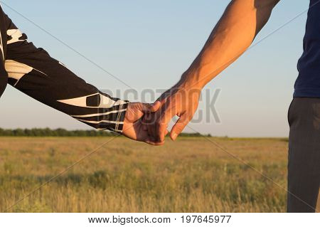 Old and adult person holding hand on the background of the ripe field. Elderly care and respect. Mother and son.