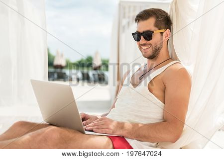 Portrait of joyous young man with beard in sunglasses sitting on lounger and leaning back on its pole with curtain. He is typing something on laptop and smiling. River beach on background