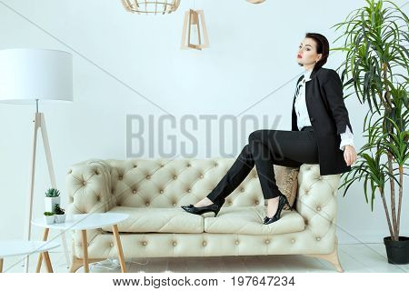 Brave and beautiful woman in a man suit sitting on a sofa in shoes.