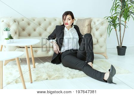 Beautiful woman in a business suit sitting on the floor she misses.
