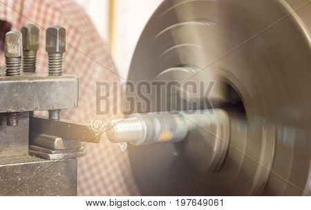 Men are using a lathe to make thread from the steel shaft