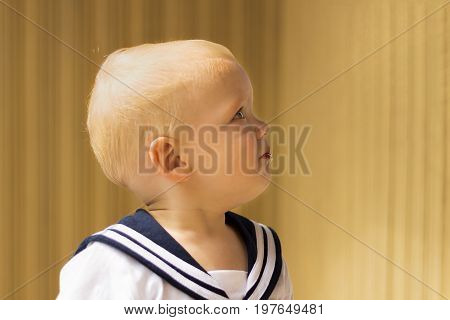 Portrait Of Funny Baby Boy In A Seaman's Suit Standing Against Wooden Wall.