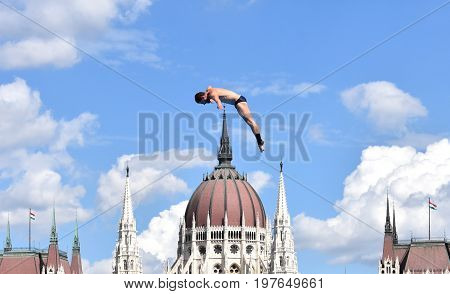 Budapest Hungary - Jul 28 2017. Man dives from the 27 metre platform during the semi-final day of men`s High Diving at the FINA World Championships. The Hungarian Parliament in the background.