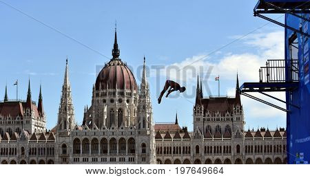 Budapest Hungary - Jul 30 2017. Blake Aldridge dives from the 27 metre platform during the final day of men`s High Diving at the FINA World Championships. Hungarian Parliament in the background.