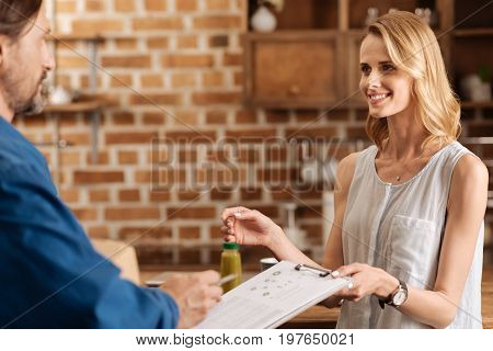 Here you go. Friendly lively dedicated woman receiving a delivery from a store and confirming it by singing some papers for courier