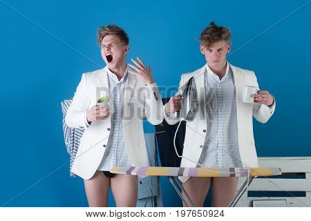 Businessmen wearing shirts jackets and underpants. Macho yawning with cup of energetic drink. Man holding iron at ironing board. Clothes rack in dressing room. Fashion.