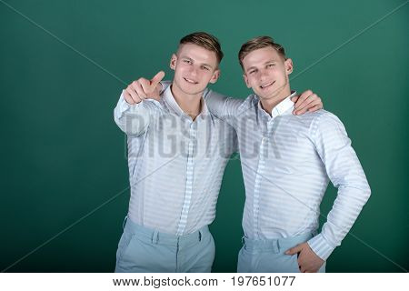 Two Brothers Smiling And Pointing Finger