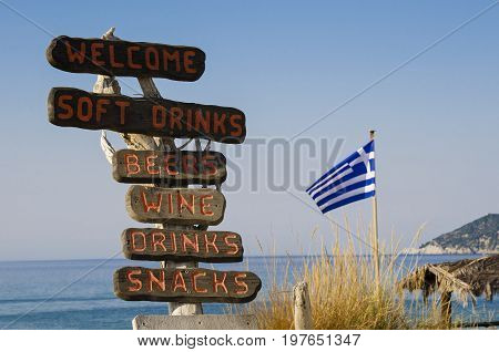 Wooden signposts on the beach indicate the presence of a bar offering food and drink in Skiathos Greece on the bottom the Greek flag