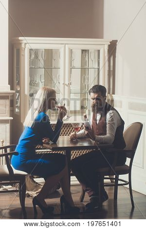 Girl and hipster dating in restaurant. Woman with blond hair and man drinking wine from martini glasses. Couple in love. Alcohol and appetizer. Addictive and convive. Unhealthy lifestyle. Bad habits