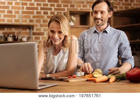 This looks nice. Energetic sincere ambitious woman finding nice meal online and looking through cooking instructions while managing husbands actions