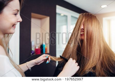 Female customer with long straight fair hair laughing while a hairdresser combing out strands in front of her face working in beauty salon