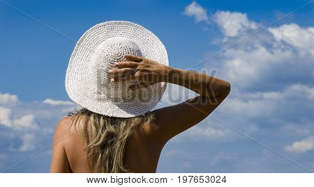 Young Girl Turned Back, Holding Her Hat With Her Hand