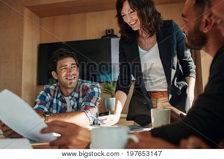 Shot of business people discussing in meeting room at startup. Office workers discussing new business plan together in board room.