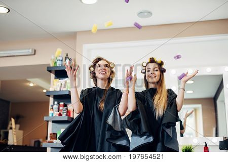 Two female customers of beauty salon standing in hair rollers having fun playing laughing.