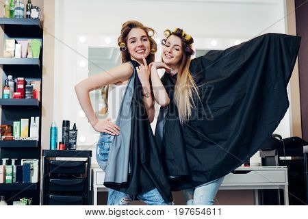 Portrait of two pretty blondes wearing hair rollers and cape standing in funny silly pose looking in camera at hairdressing and beauty studio.