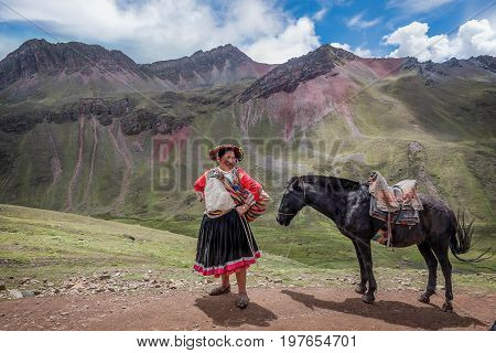 Cusco, Peru- March 18, 2017: Woman with a horse on Vinicunca aka Rainbow Mountain in the region of Cusco Peru