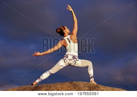 young caucasian fitness woman practicing yoga outdoors