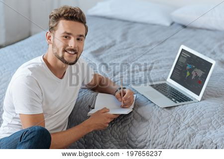 Show your smile. Handsome freelancer sitting opposite his computer and keeping smile on his face while going to make notes