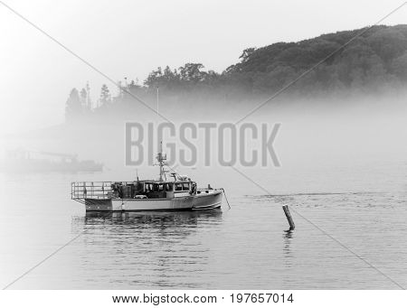 Lobster fishing boat on misty waters in Maine