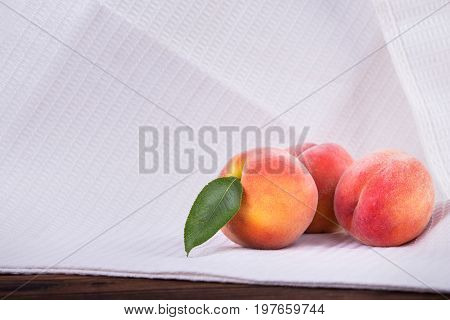 Close-up of a three whole and juicy peaches on a white table-cloth. Appetizing fruits of peaches or nectarines with green leaves full of vitamins on a light fabric. Summer fruits. Vegetarian lifestyle