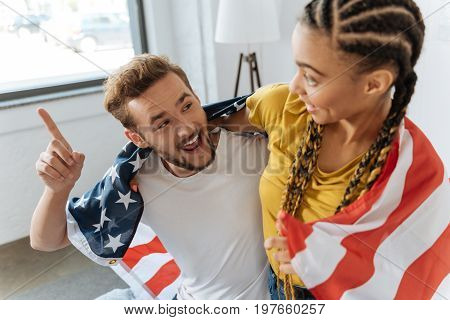 Hey you. Positive bearded man keeping smile on his face and raising eyebrows while showing his forefinger