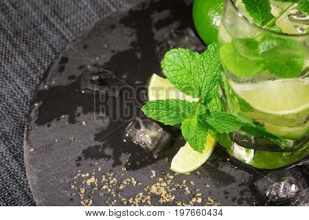 Top view of summer mojito drink with rum, lime, mint, ice and brown sugar on a dark background. A glass full of alcohol drink from lime, rum, mint and cubes of ice. Non-alcohol cocktail. Cold drinks.